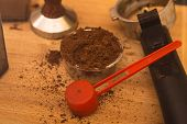 Coffee Tamper With Coffee In Filter Basket And Filter Holder On A Board poster