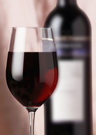 stock photo of red wine  - red wine glass with bottle in background - JPG