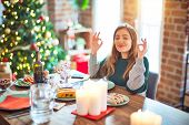 Young beautiful woman sitting eating food around christmas tree at home relax and smiling with eyes  poster