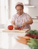 Senior Hispanic woman chopping vegetables
