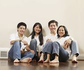 Portrait of Asian family on floor