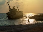 Silhouette Of A Girl On Sunset Near The Old Ship On The Mediterranean Sea Background. The Old Edro I poster