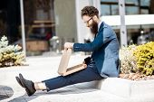 Hungry Businessman Dressed In The Suit Eating Pizza While Sitting On The Street Near The Office Buil poster