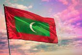 Fluttering Maldives Flag On Colorful Cloudy Sky Background. Maldives Prospering Concept. poster