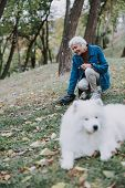 Elderly Lady Staying With Cute Pedigree Dog Outside poster