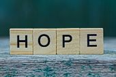 Word Hope Made Of Wooden Letters On A Gray Table On A Green Background poster