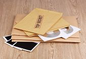Envelopes with top secret stamp with photo papers and CD disks on wooden background