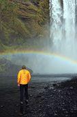 Tourist admiring the Skogafoss Waterfall, famous natural landmark in Iceland, Europe poster