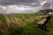 Lonely Bench In A Cold And Windy Coastal City, Pointing To The Sea With Dramatic Cloudy Sky While Gr poster