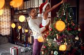 Happy Father and daughter having fun together and putting ornaments on the Christmas tree poster