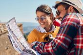 Choose a destination at travel.Smiling man and woman traveling and reading map in city poster