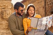 Happy man and woman on vacation sightseeing city with map poster