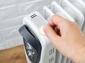 Woman Hand Putting A Coin Into Home Electric Oil Heater. The Concept Of Higher Electricity Costs Dur poster