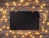 Blank Chalkboard Sign With String Lights Hanging From Wooden Background. poster