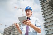 Frustrated site manager using his tablet in front of a construction site poster