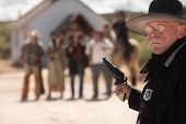 image of gunfighter  - Outgunned sheriff in old American west showdown - JPG