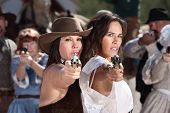 stock photo of gunfights  - Pretty female gunfighters with pistols at point blank range - JPG