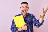 Young handsome student man holding a book over isolated background very happy and excited, winner ex poster