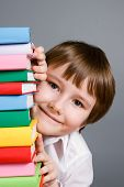 Boy Looks Out From A Stack Of Books