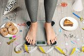 Woman Using Scale Surrounded By Food And Alcohol After Party On Floor. Overweight Problem poster