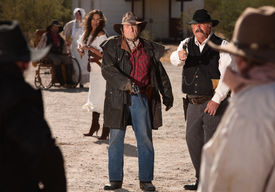 stock photo of gunfights  - Angry male and female gunfighters pull out their weapons - JPG