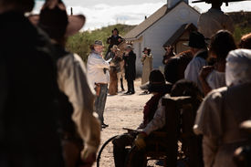 pic of gunfights  - Cocky gunfighter waves back crowd in an old west showdown - JPG