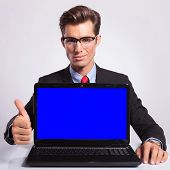 elegant young business man presenting a laptop and showing thumb up sign while looking at the camera with a reassuring expression