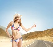 Young and sexy girl in American swimsuit makes the hitch-hiking