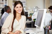 Woman Working At Desk In Busy Creative Office