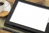digital tablet computer in black leather case with white blank screen isolated with clipping path, stylus pen, coffee cup and cookie