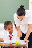 beautiful female primary educator tutoring student in school