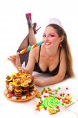 smiling girl with sweets and candies lying on the floor