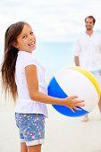 Pai e filha brincando na praia juntos se divertindo com beachball
