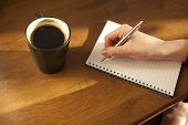 Womans hand with notepad and coffee
