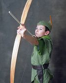 stock photo of fletching  - Young Robin Hood drawing a bow and arrow - JPG