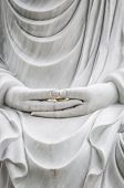 Buddha statue with hands as main subject.