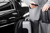 stock photo of cabs  - Traveling Businessman with His Luggage Using Phone - JPG