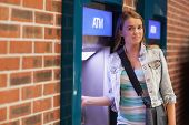 Pretty happy student withdrawing cash smiling at camera at an ATM