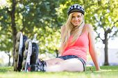 Casual cheerful blonde wearing roller blades in a park