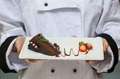 Chef presenting chocolate cake with strawberries on white plate