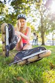 Casual pretty blonde wearing roller blades and helmet in a park