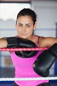 Portrait of a beautiful young woman in black boxing gloves in the ring