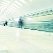 Train in motion blur and blurred people in subway station.