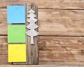 colorful reminder notes attached on a old wooden signboard with paper christmas tree