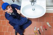 Smiling plumber repairing sink showing thumb up in public bathroom