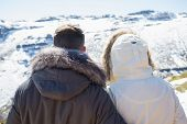 Close-up rear view of a couple in jackets looking at snowed mountain range