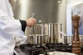Head chef stirring in pot in professional kitchen