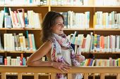 Side view of a smiling female student with books standing in the library