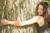 Casual happy brunette embracing a tree with closed eyes in a park on a sunny day