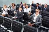 Image of business people sitting in rows at seminar with raised arms